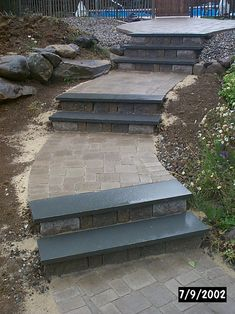 Paving stone walkway around a pool, with bluestone stairs featuring belgian block risers