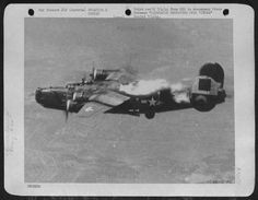 This Consolidated B-24 Liberator of the U.S. Army 15th AF was mortally struck by a German Bf 109 during a mission over the synthetic oil refineires at Vienna, Austria. Flames are seen bursting out behind the wings and sweeping back toward the tail. The Liberator exploded before for its final plunge. One crew member managed to bail out safely before her loss. Note the crew member coming out of escape hatch.