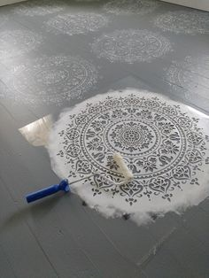 stenciling gray and white floor with mandala stencil and foam roller
