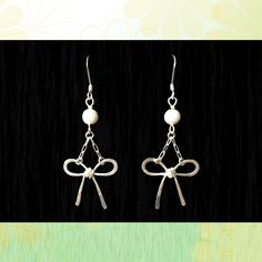 "These cute Ribbon Bow Earrings are made of sterling silver and dangle from a fish hook styled earrings. Each bow was carefully shaped out of 20 gauge sterling silver wire and the gently hammered to give it a ""ribbon-like"" appearance. Simple and chic, these earrings are fun, playful, and fabulously girly!  All the components of the earrings are sterling silver and the earrings measure 3/4""W and hang about 1 1/2"" from the earlobe."