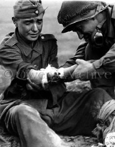 A captured teenage Nazi is in tears as he holds out his wounded arm for a sympathetic American to examine as they wait for a medic in Cherbourg. The French were sometimes puzzled (and angered) by Americans' kind treatment of prisoners, including giving them oranges, which they had not seen for years.  God Bless America!!