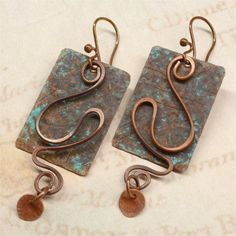 These earrings are hand forged from annealed copper which I hammered and gave a verdigris patina. I used annealed copper wire to form swirl shapes in