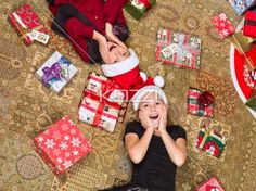 top view of shocked kids lying on floor. - Top view of shocked kids lying on floor with christmas presents on the side, Model: Shania Chapman - Agent is Breann at MMG. breann@nymmg.com and Josh Chapman