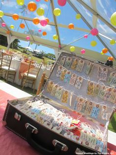 To get that vintage travel look for their wedding, the couple had luggage tag shaped tags strung inside a vintage suitcase packed with items for their honeymoon. Stickers of Hawaii locales adorned the outside of the suitcase. We decorated the clear top tent from Pacific Party Rentals with 120 colored lanterns, but only 20 were lit. Natural chiavari chairs from PPR. Les Saisons provided specialty linens www.les-saisons.net.Wedding planned by Hawaii Weddings by Tori Rogers…