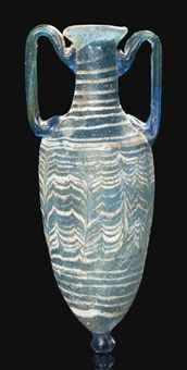 A GREEK CORE-FORMED GLASS AMPHORISKOS  HELLENISTIC PERIOD, CIRCA 2ND-1ST CENTURY B.C.  With dark blue body, tall neck and everted rim, wound with opaque white trails tooled into a feather pattern around the body, with applied blue twin handles and knob base  5¾ in. (14.5 cm.) high