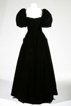 A Christian Dior black 'Princess de Cleves' silk velvet evening gown, probably Spring-Summer, 1957. Patron Original label and numbered 45129, the bolduc numbered 677966 and model name tag, with broad puffed sleeves, corsetted bodice, full skirt over horsehair, tulle and silk petticoats, bust 82cm, 32in, waist 61cm, 24in For a similar dress see The Metropolitan Museum of Art: http://www.metmuseum.org/collections/search-the-collections/94751?img=0.