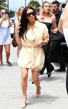 Kim Kardashian wore a beige shirtdress with a tie that honed in on her waist. The 'Keeping Up With the Kardashians' star paired the look with matching taupe-colored sandals and loose hair. See what the other Kardashians wore!