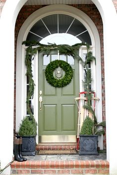 Green Christmas front door, boxwood wreath, vintage sleigh, holiday decorating