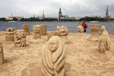 People walk past sand sculptures at the Magic Sand Riga festival in Riga, Latvia, July 5, 2011. The festival, hosted in Riga for the first time, features creations by 12 international artists. (Xinhua/Reuters Photo)