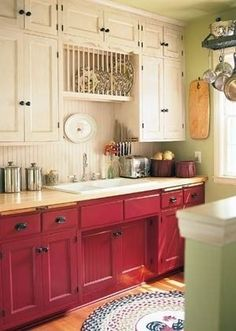 LOVE the cottage feel of this kitchen. The old cabinets both white & red with the wood backsplash. Not sure like the mint green wall color.