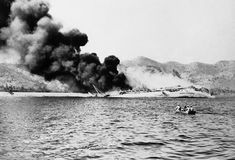 August 3, 1942: After hammering Port Moresby for two days, Japanese bombers finally sank this Australian transport which sends up a cloud of smoke.