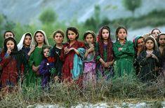 Meninas afegãs observam equipe da ONU descarregando material usado nas eleições em Cabul. Afeganistão, 04/10/2004. Foto: Emilio Morenatti/AP