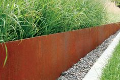 MODERN steel retaining wall, grass & small grey rocks for front yard.