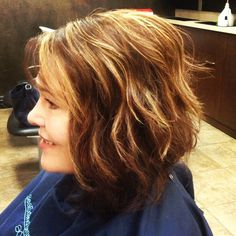 Warm brown base with honey blonde hi-lights. Styled with a loose flat iron curl.