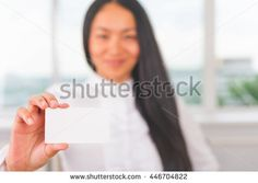Asian businesswoman holding a business card for your contacts: mobile phone, fax, email, web site. Relation and communication. White blank with copy space