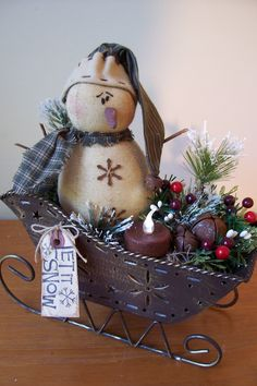 Repurposed Metal Sled with a cute snowman, sprigs of pine, burgundy berries, frosted ming pine, glittery fern leaves, rusty jingle bells, grungy cinnamon rolled tea lite and a prim stained tag that says 'Let it Snow'. $19