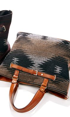 Woven tribal print bag made from fabric with faux leather trim, top handles, removable shoulder strap and inside snap closure.