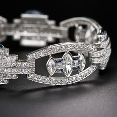 A spectacularly designed and executed platinum, diamond and sapphire bracelet circa 1925. The four main links are each set with three floating marquise diamonds punctuated with two square-cut diamonds bordered by french cut calibre sapphires.The stepped diamond connector links are crowned with unusual custom cut buff-top sapphires. A truly stunning and superb bracelet, the quintessence of Art Deco modernism.