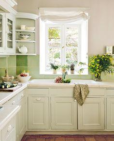 Cocina con azulejos verdes y muebles en blanco. Muebles en blanco
