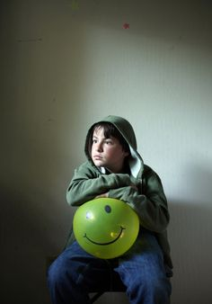 """timothy archibald, """"Echolilia: A Father's Photographic Conversation with his Autistic Son"""". redux pictures.  I wanted an image that touched on clinical depression in children, or maybe something that represented a general mood disorder. The smiley balloons were a natural prop, but Eli's mile-long stare is what held the image together and gave it its soul (....)  http://lightbox.time.com/2010/10/25/echolilia-a-fathers-photographic-conversation-with-his-autistic-son/#6"""