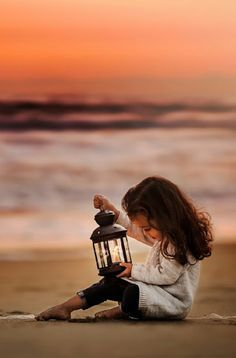 Young girl on the beach near sundown with her lantern