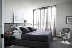 Renovation: the overhaul of an art-loving, empty-nester's Melbourne apartment: The bedroom is almost exclusively black, grey and white, with sheer curtains to let in natural light to the smalll space.