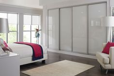 Sliding wardrobes are a versatile fitted bedroom design, white glass bedroom furniture gives the opportunity to bring colour through accessories #fittedwardrobes #whitebedroom #slidingwardrobes #bedroom #bedroomfurniture
