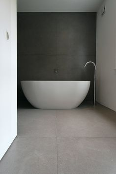 Minimalist Bathroom // oversized tub with dark wall provides the perfect contrast by LBMVarchitects, Queens Park, London