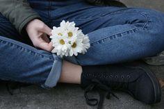 Sentada,  de botinha, calça dobrada, e flores