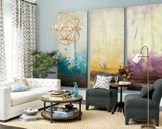Use a series of paintings to fill a blank wall in a living room