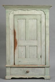 Green-painted Cupboard over Drawer, possibly New England, c. 1840, the cove-molded cornice over a single hinged paneled door opening to shelves, framed by a cutout applied border, the ends with recessed panels with arched tops, original surface, (minor imperfections), ht. 74, case wd. 43 1/4, case dp. 14 in.