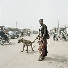 Sadly, this is not a loving relationship.Wild animals are brought up to perform and are kept in bondage. The Hyena Men of Nigeria by Pieter Hugo.