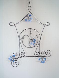 Ptačí+budka+v+modrém-+závěs+Drátovaná+dekorace+z+černého+vázacího+drátu,+dozdobená+skleněnými+korálky+v+narvě+vodově+modré,+čirými+praskanými+korálky+a+modročirými+lístečky.+Vhodné+k+zavěšení+na+zeď,+do+okna,+do+prostoru.+Velikost+budky+s+větvičkou+21+cm+x+29+cm,+výška+celého+závěsu+složeného+z+budky+a+tří+háčků+je+cca+39+cm.