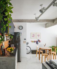 cozinha aberta com plantas, concreto e tijolinho