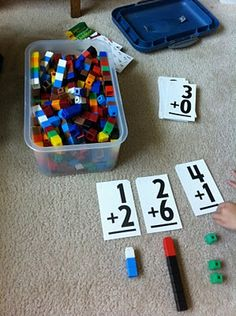 See what flashcards mean with unifix cubes or legos! 1+2 means we stack 1 cube on top of 2 stacked cubes--now we have 3 cubes stacked together! 1+2=3. Lay out the flashcards and stack cubes beneath them to make each answer. Use different colored cubes for each math problem.  For 1+2 we use 1 white cube and stack beneath it 2 blue cubes to give us the 3 total cubes.