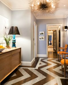 A bold chevron pattern painted on lighter hardwoods definitely gives a livelier look. But the neutral color scheme ensures the floors look great with any decor.
