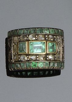An emerald and diamond ring, late 18th/early 19th century  The broad domed rectangular panel set with three step-cut emeralds, within a surround of rose/lasque-cut diamonds, between borders of calibre-cut emeralds, to scrolled foliate shoulders