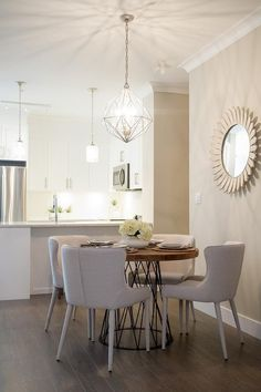 A round wood and iron lattice dining table sits surrounded by modern light gray linen dining chairs lit by a gold geometric light pendant reflected in a gray sunflower mirror mounted to a soft gray wall.
