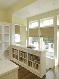 Take ugly devider railing out and put in  bookcase same height as railing to house cookbooks in kitchen, drawers for silverware or linens