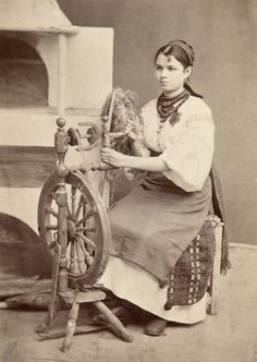 A Ukrainian woman in traditional dress works a spinning wheel.