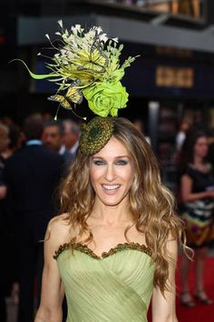 Philip Treacy Tall hat I love this design because it has the rose at the bottom and it looks realisic. I like the thin leaves that shoot out at the top, they look really good. The green colour also matches her dress and green is a main colour in plants, which adds to the theme of floral.