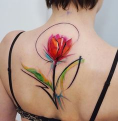 Fully bloomed red tulip tattoo on the base of the neck. An almost abstract looking tulip tattoo that plays with multi colors giving it a vibrant look.