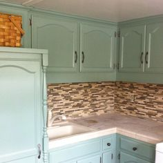 "Laundry cabinets painted with Valspar ""Seafoam Sage."" Travertine countertops & glass backsplash. Love!"
