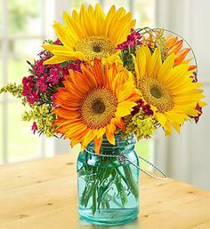 Sunflower yellow and orange floral combination looks stunning in a blue tinted mason jar