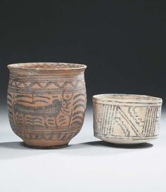 Indus valley pottery jar and a cup.   2300 - 2000 B.C. and 3300 - 3000 B.C.   The slightly ovoid shaped jar is painted in black with a pair of bulls separated by a tree and placed between geometric bands; the cup painted with a black geometric design  12 and 11 cm diameter (2)