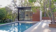 12 Modern Pools: Studio William Hefner designed this pool house and home in Brentwood. The smooth pavers surrounding the simple pool let's the horizontal wood slats on the structure and fence be the stars.