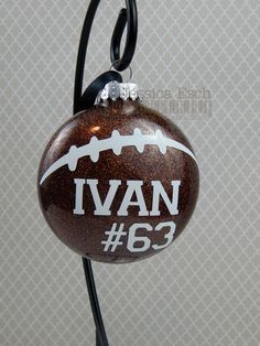 Personalized Football Glass Ornament..Customized to match your team colors Ornament is a 3 M&M shaped glass ornament that is hand glittered and