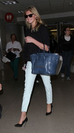 Kate Upton looks stunning walks through LAX in Ray Ban's, white trousers, black pumps and a blue crocodile skin purse.  Pictured: Kate Upton