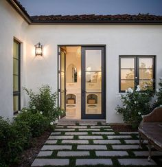 Beautiful courtyard features a French settee placed atop grass pavers illuminated by an iron outdoor sconce.