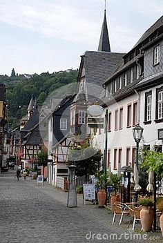 Photo taken in a center called Bacharach along the Rhine valley in Germany. In the picture you see the main street of the small town. To the right of the paved street of stones you see in the foreground the outside of a coffee with a lamppost two chairs umbrellas closed some plants and flowers. Note also on the roofs of the houses the tip of the bell tower and the woods beyond the housing.